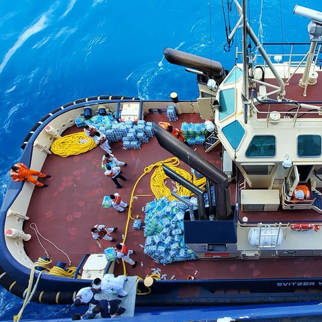 Thousands of Bottles of Water Being Loaded onto a Tug From Celebrity Equinox