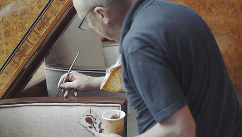 worker paints trim on qm2